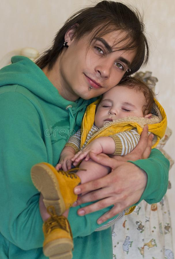 Man holding a sleeping baby in his arms. Young men holding a sleeping baby in his arms. this is father and son, or two brothers stock images