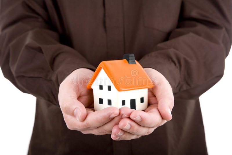 Man holding a small house. In his hands stock images