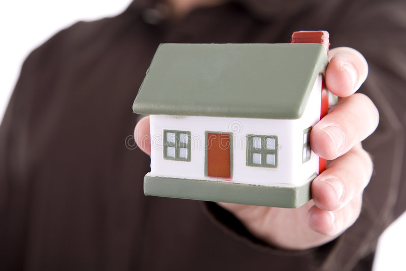 Man holding a small house. In his hand stock images