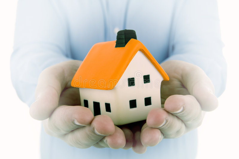 Man holding a small house. In his hands with dream effect to enphasize the house stock images