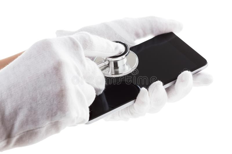 Man is holding smart mobile phone with phonendoscope tools on screen. Man is holding smart mobile phone with phonendoscope, stethoscope on screen stock image