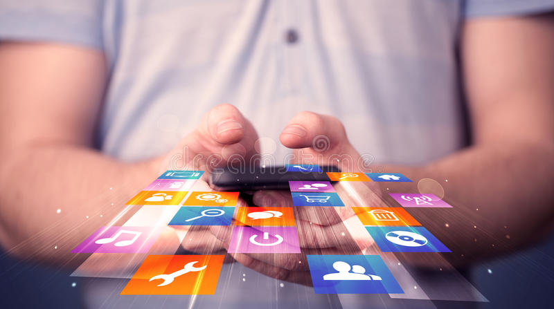 Man holding smart phone with colorful application icons. Comming out stock images