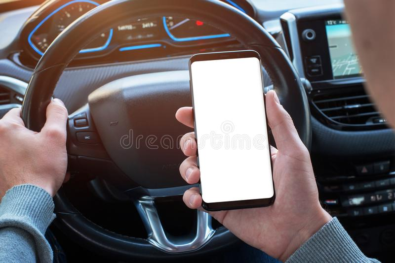 Man holding smartphone in car with isolated, white display for mockup, app, or web site design promotion. Modern car interior in background stock image