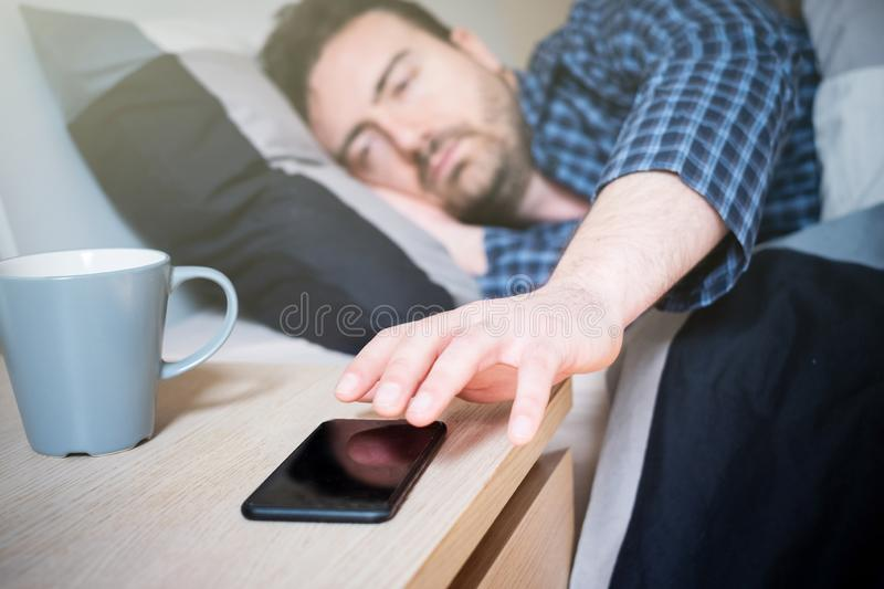 Man holding smartphone lying in his bed. Man using mobile phone in bed at home in the morning stock photography