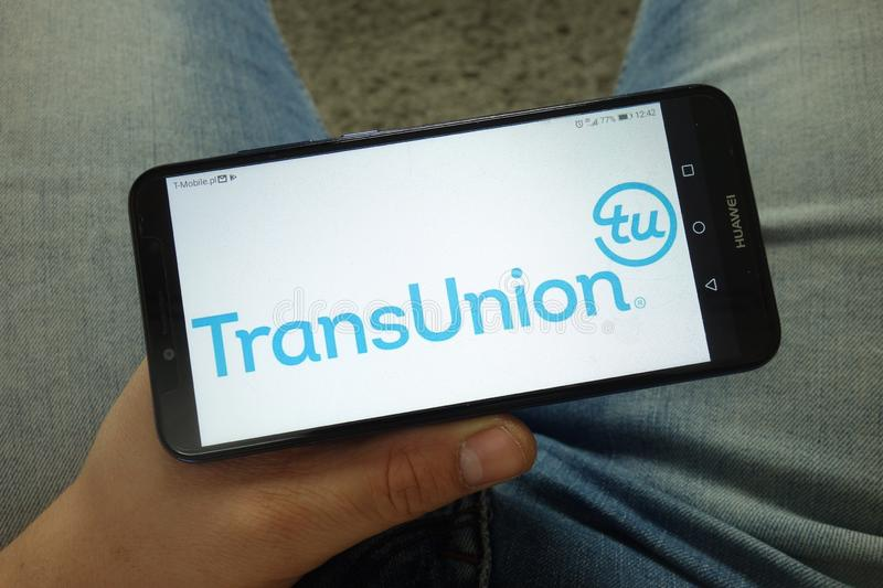 Man holding smartphone with TransUnion American consumer credit reporting agency logo stock image