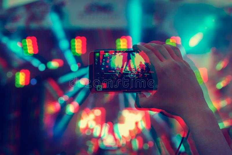 Man holding smartphones in hands and photographing and shoots a video. Taking photo on front stage on summer outdoor music concert. Festival. Digital signal royalty free stock photography