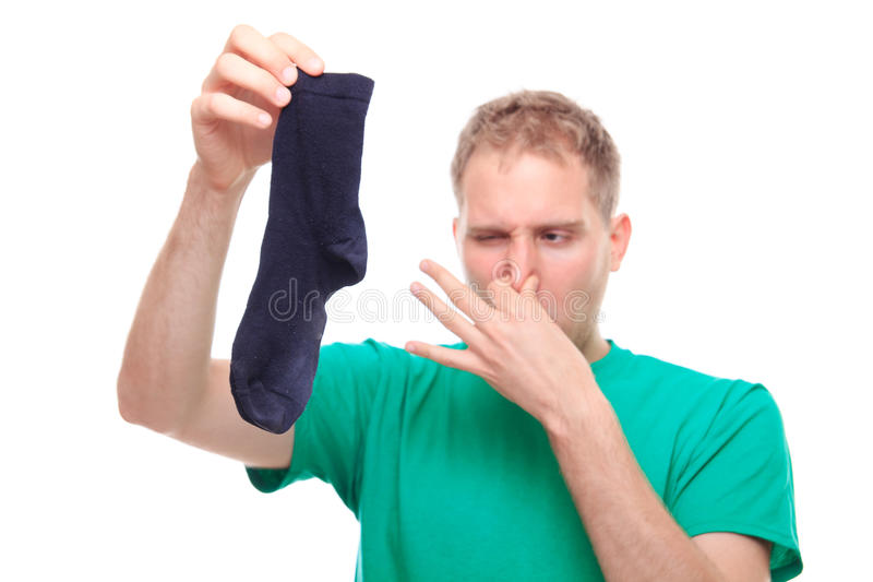 Man holding smelly socks and clogged nose. Studio shoot stock images