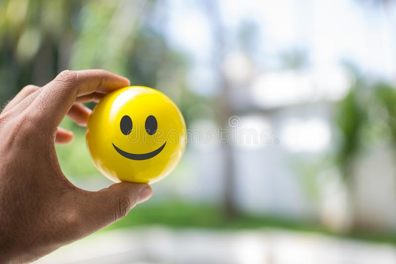 Man holding a smiley ball in hand stock images