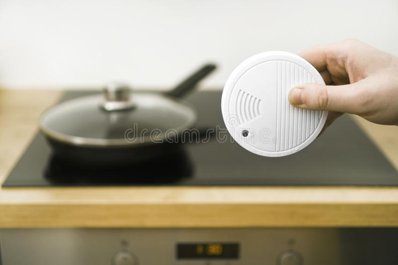 Smoke detector. Man holding smoke detector in the kitchen royalty free stock photography