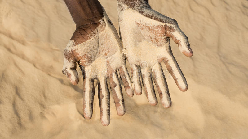 Man holding some sand in the hand. The problem of desertification stock photo