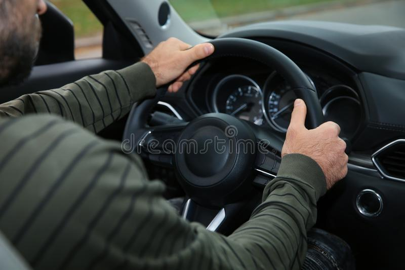 Man holding steering wheel in car, closeup. Driving test. Man holding steering wheel in car, closeup. Driving license test royalty free stock images