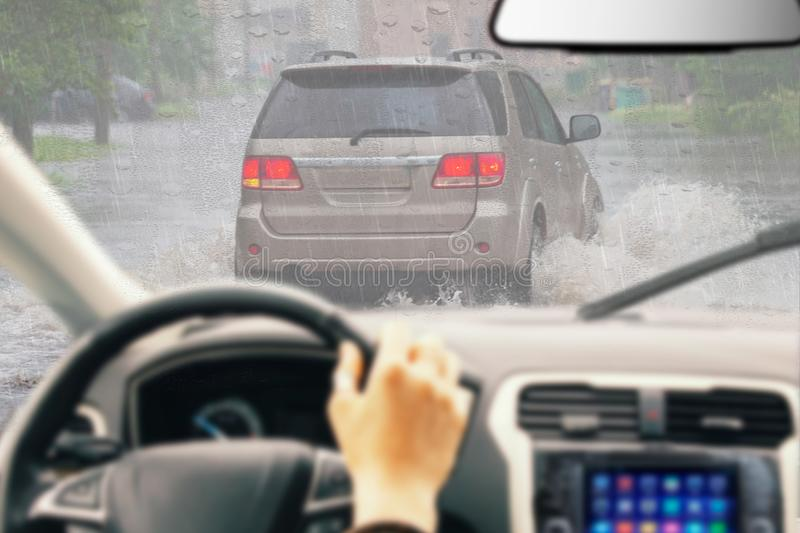 Man holding steering wheel, driving a car in the rain, careful driving in rainy day, right hand drive royalty free stock photos
