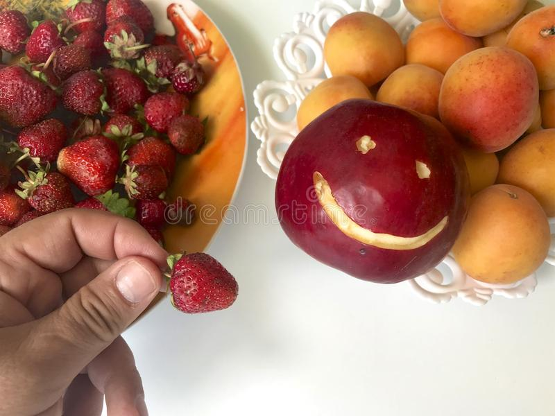 The man is holding strawberry in his hand 她握她的手到草莓板材  下个盘用杏子和苹果 免版税库存图片