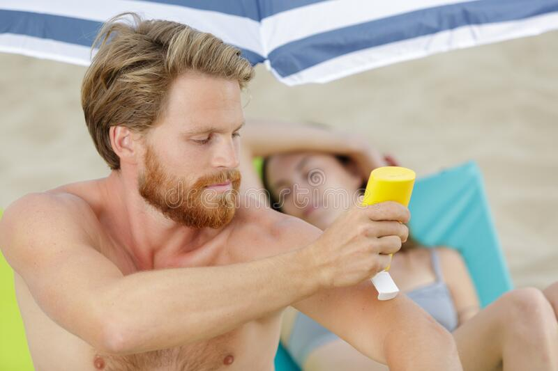 Man holding sunscreen bottle in hand royalty free stock images