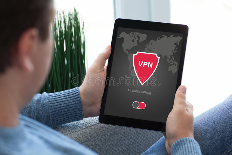 Man holding tablet app vpn creation Internet protocols protection network. Man holding tablet with app vpn creation Internet protocols for protection private stock photos