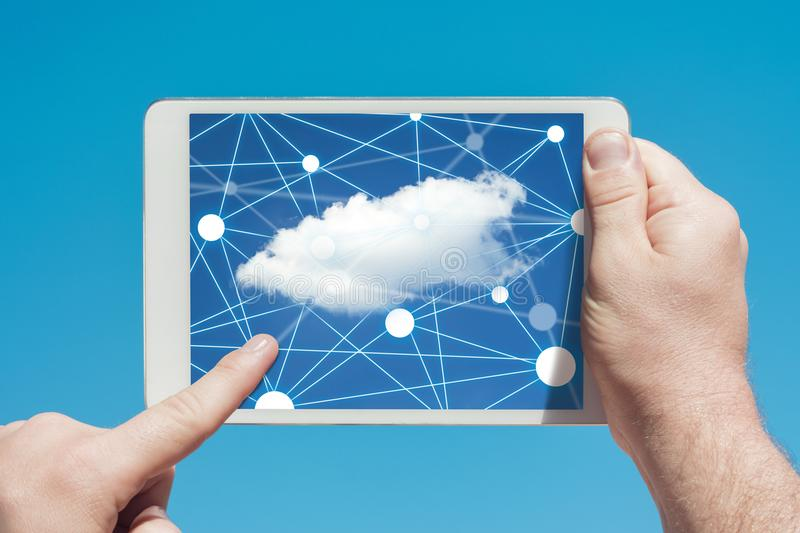 Man holding a tablet device and cloud computing communication icon to download stored data stock photography