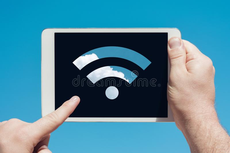 Man holding a tablet device showing wifi sign and touching the s royalty free stock images