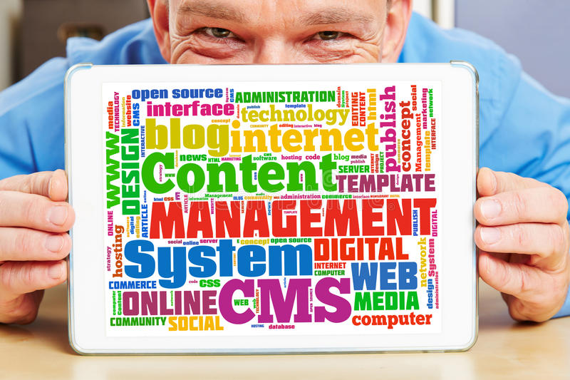 Man holding tablet PC with CMS tag cloud royalty free stock photos