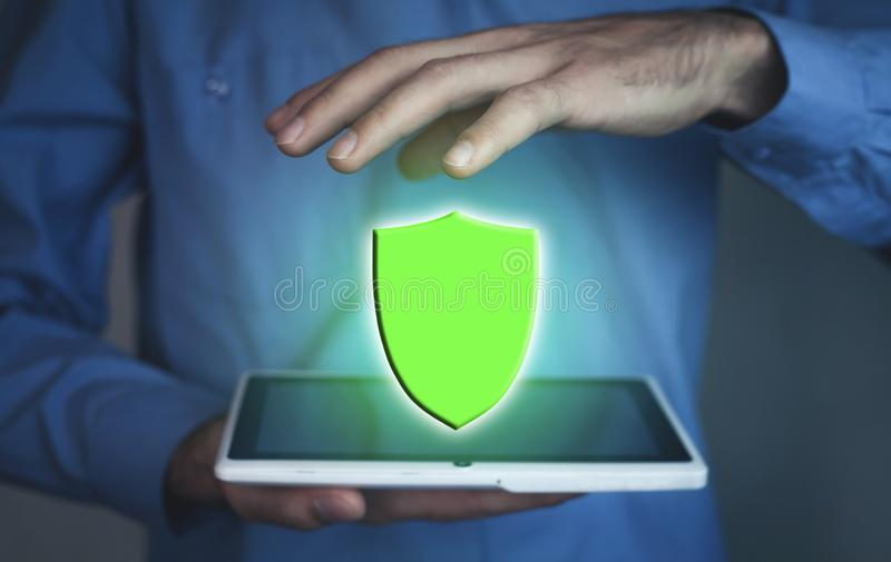 Man holding tablet with a shield protection royalty free stock photos