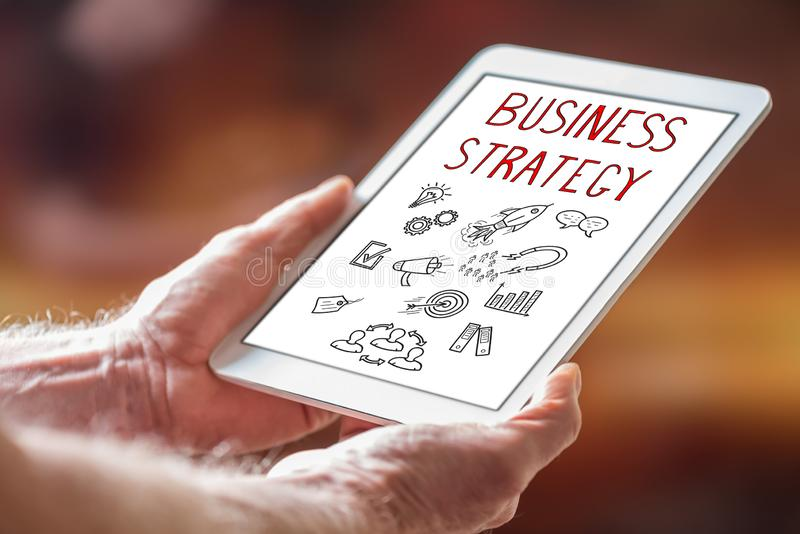 Business strategy concept on a tablet. Man holding a tablet showing business strategy concept stock images