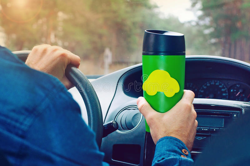 Man holding thermo mug with sticker label. Close up of male`s hands holding thermo mug with empty car-shape sticker label driving a car royalty free stock photos