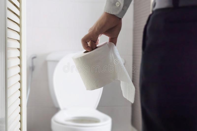 Man holding tissue paper standing next to toilet bowl royalty free stock image