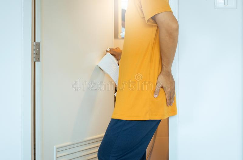 Men holding toilet paper and using toilet with suffering from Diarrhea and Hemorrhoids after wake up in morning at home,Copy space. Man holding toilet paper and stock photography