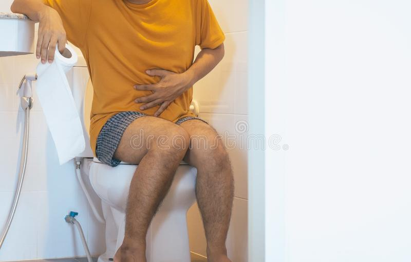 Man holding toilet paper and using toilet with suffering from Diarrhea and Hemorrhoids after wake up in morning at home. Male holding toilet paper and using royalty free stock images