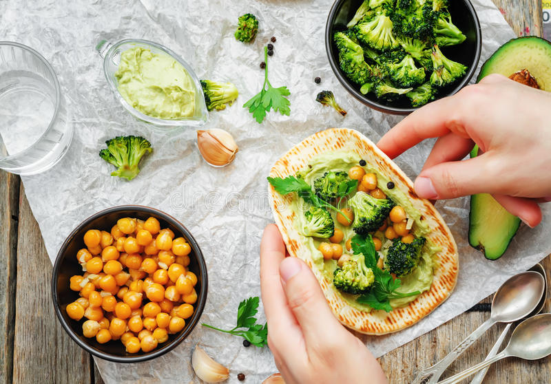 Man holding tortilla with roasted broccoli and chickpeas and avo stock photo