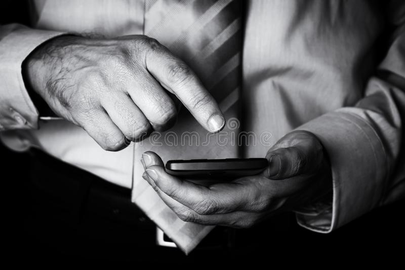 Man holding and touching screen or display with finger of a mobile phone, cell phone or smartphone. Male businessman typing a message or browsing the internet royalty free stock photos
