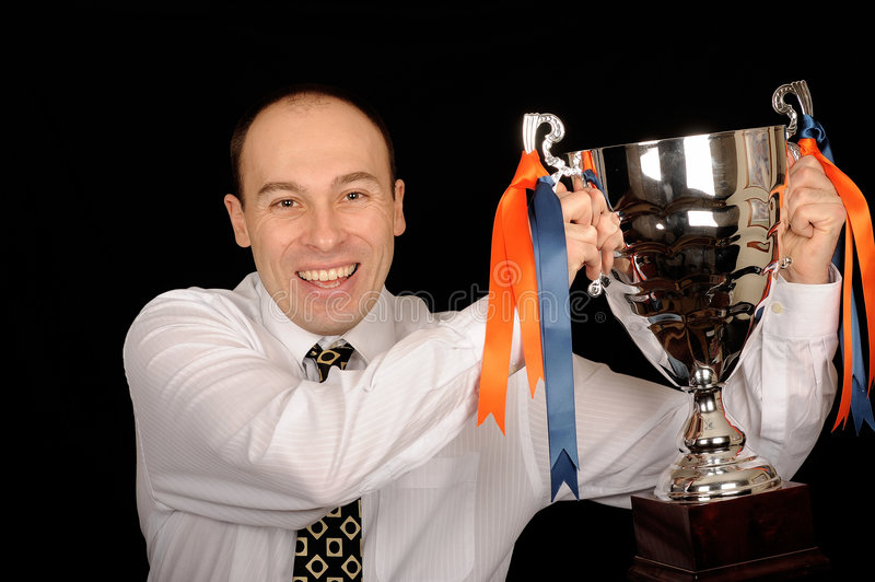 Man Holding Trophy. Businessman holding a silver trophy cup royalty free stock images
