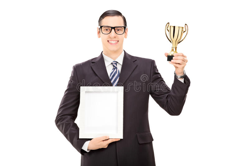 Man holding a trophy and a picture frame. Isolated on white background royalty free stock photography