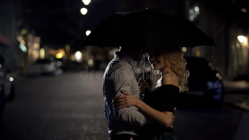 Man holding umbrella, hugging his beloved and enjoying date in the evening stock photos