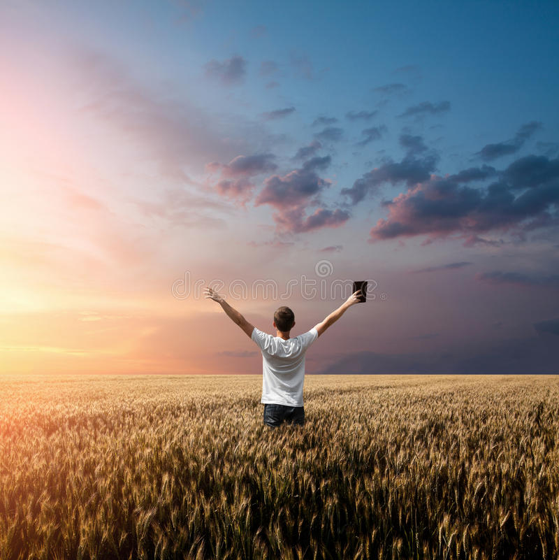 Man holding up Bible in a wheat field. With arms up stock image