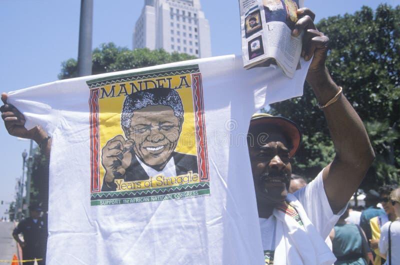 Man holding up Nelson Mandela t-shirt,