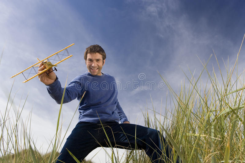 Man holding up toy airplane, standing on long grass, smiling, portrait, low angle view royalty free stock photography