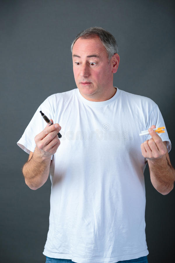 Man holding vaporizer and conventional tobacco cigarettes and comparing. Man is holding vaporizer and conventional tobacco cigarettes and comparing stock images