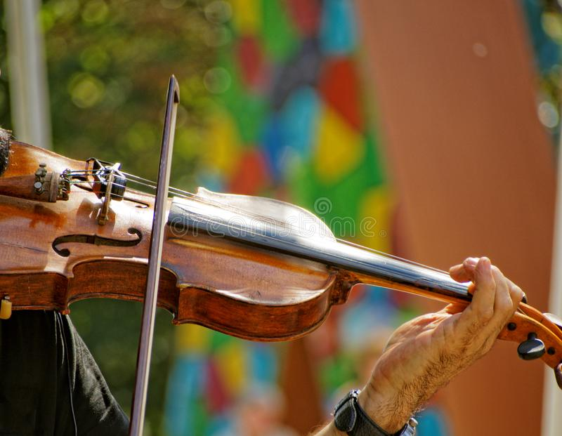 Performing on the violin. A man holding a violin and playing a musical piece on it royalty free stock photography