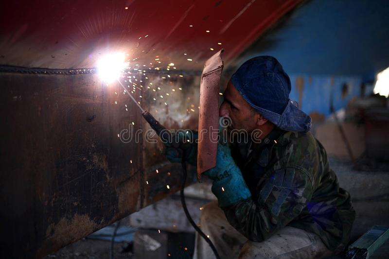 Man Holding Welding Rod and Welding Mask While Working stock photos