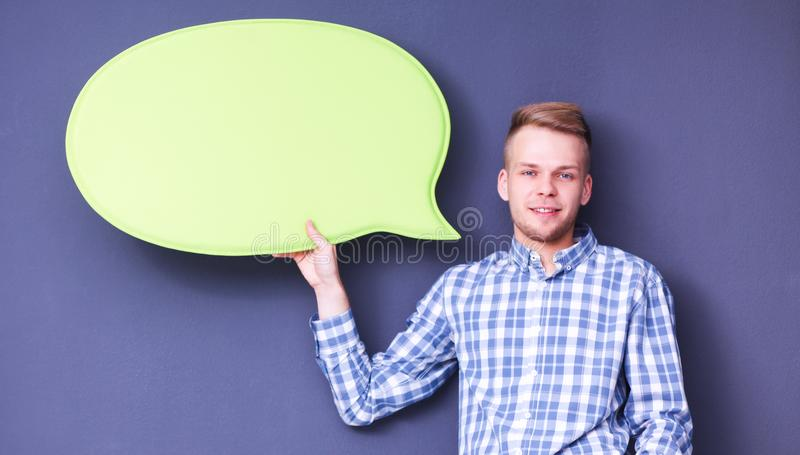 Man holding white blank speech bubble with space for text, isolated. Man holding white blank speech bubble with space for text stock image
