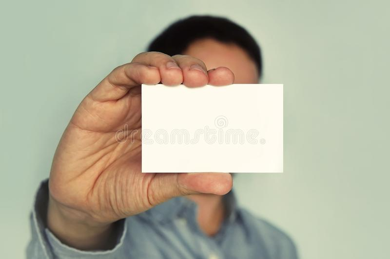 Man holding white business card on concrete wall background, businessman closes his eyes business card. Blank for text. White busi stock images