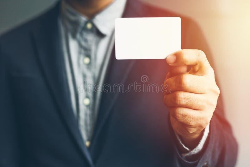 Man holding white business card,Man wearing blue shirt and showing blank white business card. Blurred background. Horizontal mocku stock image