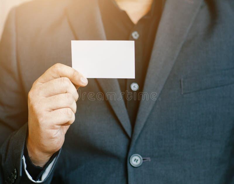 Man holding white business card,Man wearing blue shirt and showing blank white business card. Blurred background. Horizontal mocku stock photos