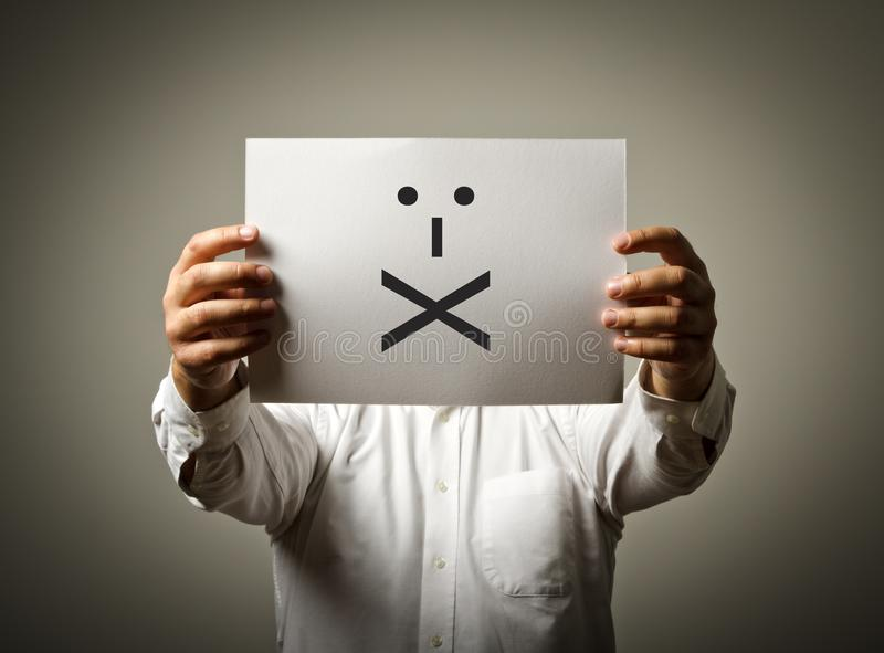 Man is holding white paper with smile. Lips Sealed. Silence concept. stock photo