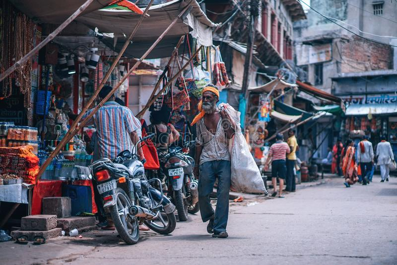 Man Holding White Sack Walking Beside Street Stores stock photo