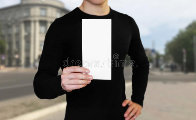A man holding a white sheet of paper. Holding a booklet. Close up. The background of the city royalty free stock photography
