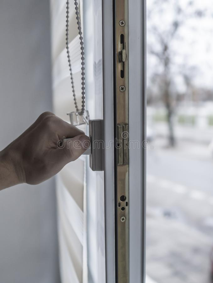Man holding window handle on a plastic window with white fabric roller blinds in the living room. Close up on roll. Curtains indoor stock photography