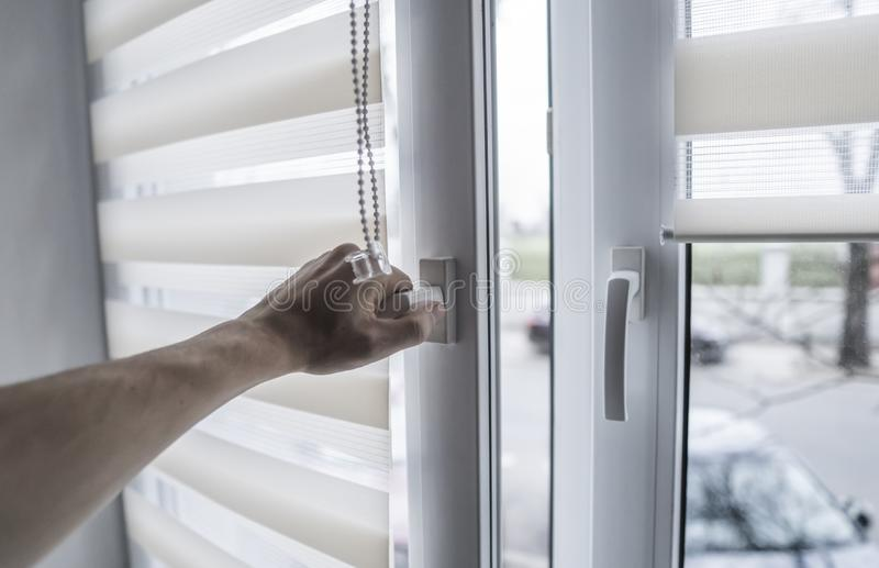Man holding window handle on a plastic window with white fabric roller blinds in the living room. Close up on roll. Curtains indoor royalty free stock image