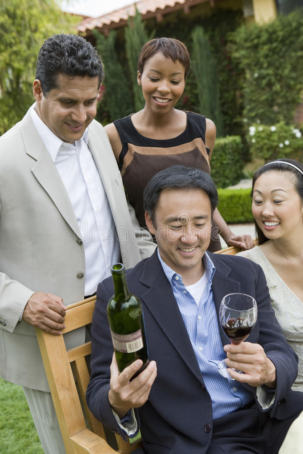 Man Holding Wine Bottle And Glass With Friends In Park royalty free stock photos