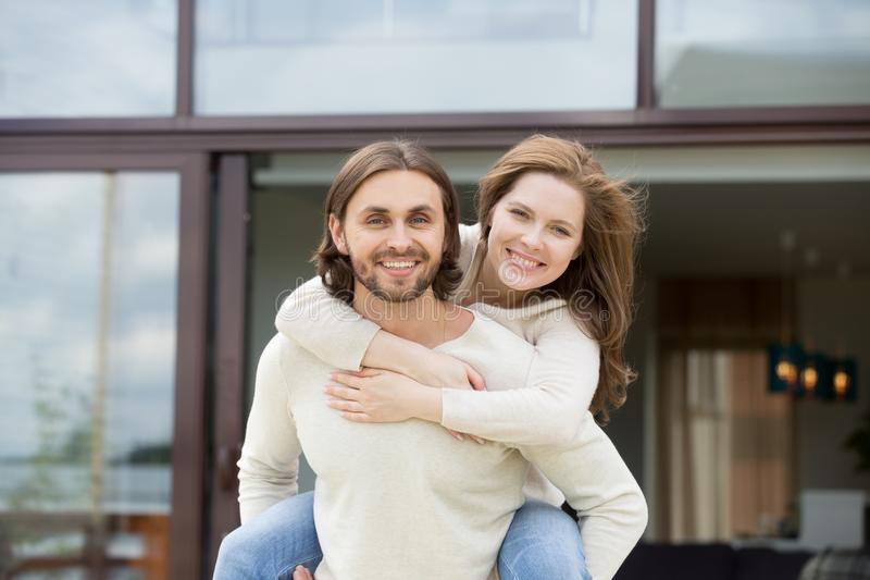 Man holding woman on back outdoors, looking at camera, portrait royalty free stock photos